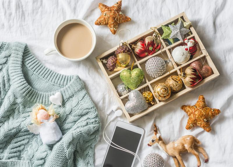 Christmas background. Box of vintage christmas decorations, coffee with milk, phone and blue knitted sweater on the bed, view from royalty free stock photo