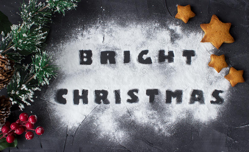 Christmas background with branch of christmas tree and baked gingerbread stars with words bright christmas made from. Powdered sugar on the concrete background stock photography