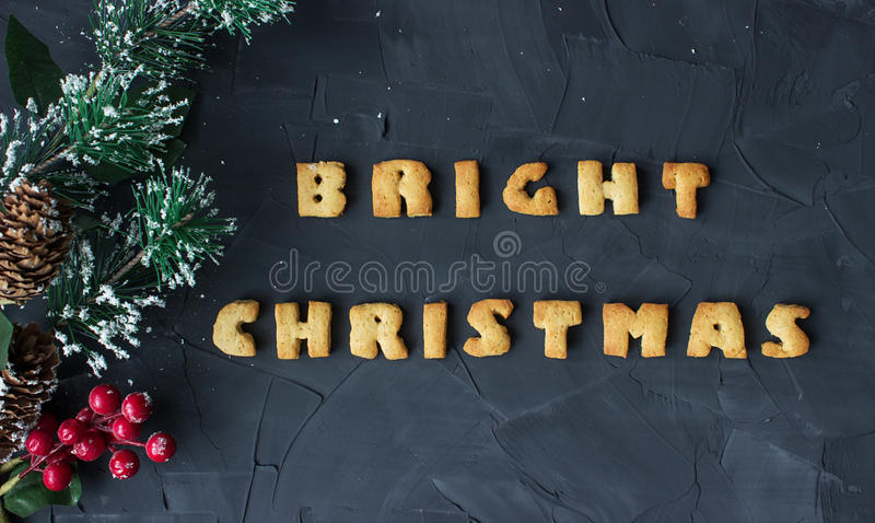Christmas background with branch of christmas tree and baked gingerbread words bright christmas . creative idea. Christmas background with branch of christmas stock images