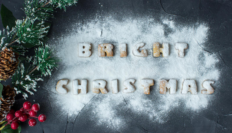 Christmas background with branch of christmas tree and baked gingerbread words bright christmas with powdered sugar. On the concrete background. creative idea royalty free stock photo