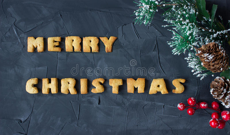 Christmas background with branch of christmas tree with baked gingerbread words merry christmas . creative idea. Christmas background with branch of christmas royalty free stock image