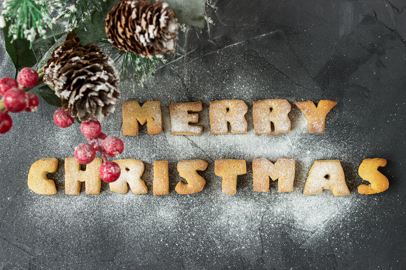 Christmas background with branch of christmas tree and baked gingerbread words merry christmas with powdered sugar. On the concrete background. creative idea stock photos