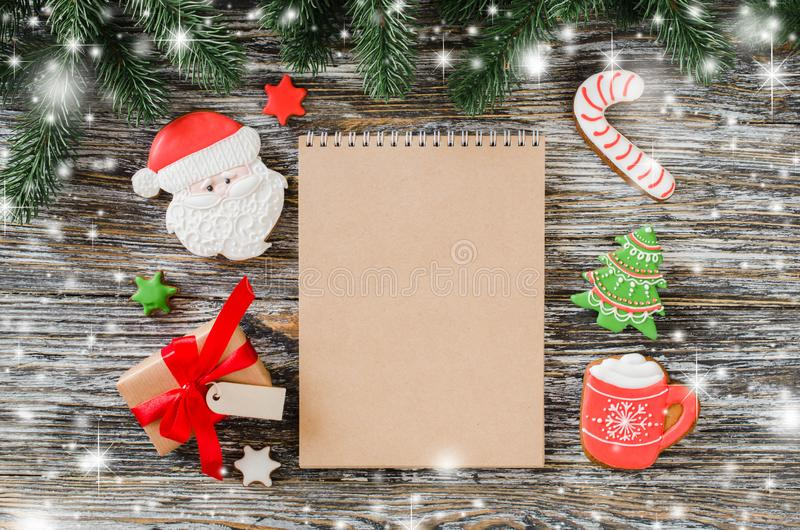 Christmas background with brown notebook and gingerbread cookies. Christmas background with brown notebook, gingerbread cookies and fir tree on rustic wooden stock photos