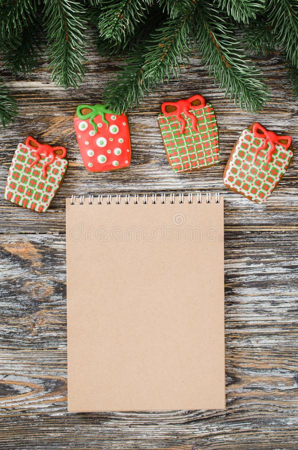 Christmas background with brown notebook and gingerbread in form of gifts. Christmas background with brown notebook, gingerbread in form of gifts and fir tree on royalty free stock photography