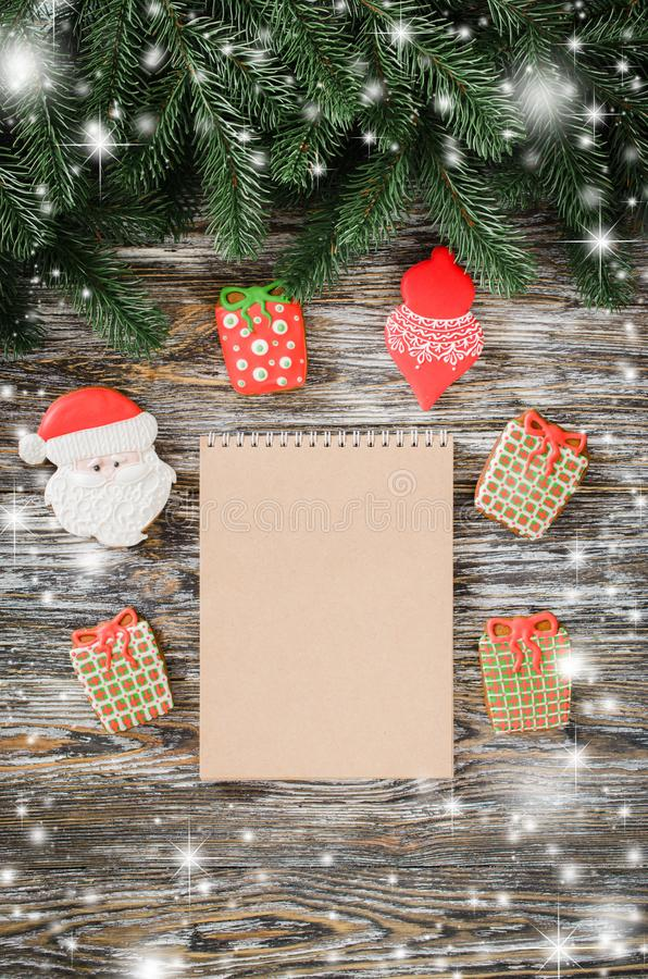 Christmas background with brown notebook and gingerbread in form of gifts. Christmas background with brown notebook, gingerbread in form of gifts and fir tree on royalty free stock image