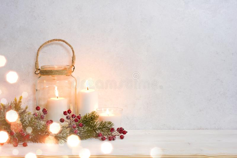 Christmas background, burning lantern candles decorated with frosted fir branches.  stock photos