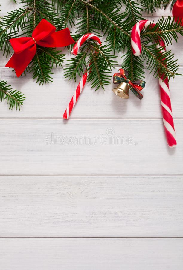 Christmas background with candies and fir tree border on wood stock photo