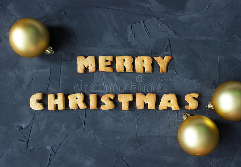Christmas background with Christmas balls and baked gingerbread words merry christmas . creative idea. Christmas background with Christmas balls and baked royalty free stock photography