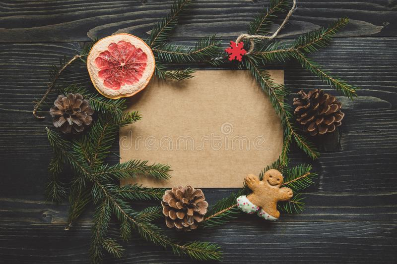 Christmas background. Christmas decoration with fir branches and gingerbread man cookie on the wooden table. royalty free stock image