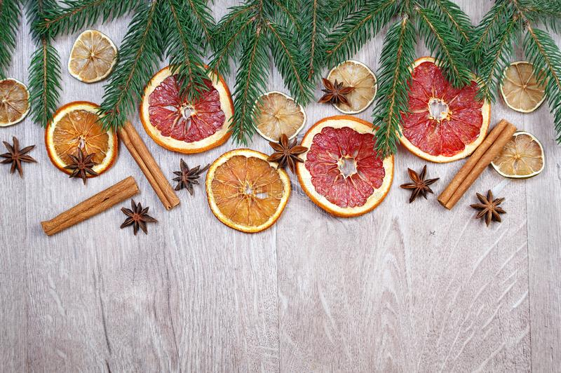 Christmas background. Christmas tree branches, dried citruses, cinnamon sticks and anise stars on a wooden table. mulled wine ingr stock image