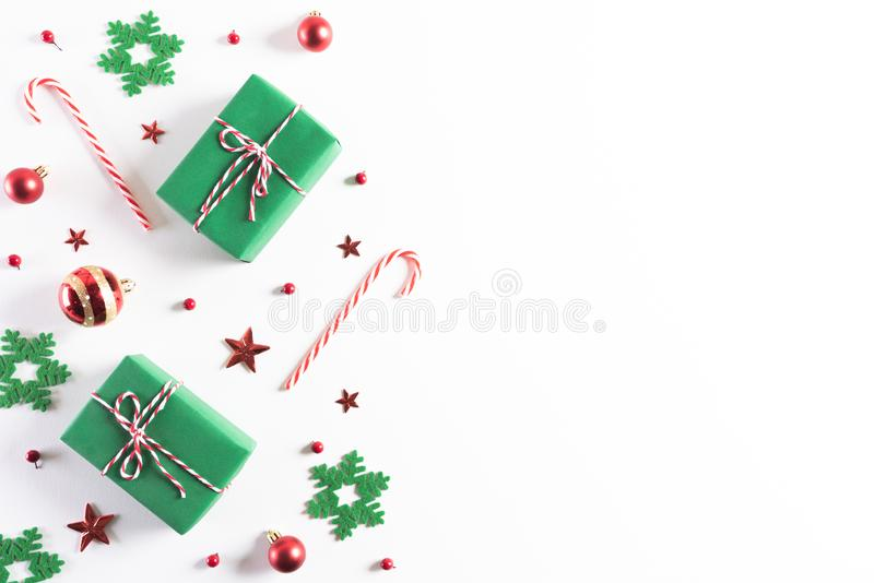 Christmas background concept. Top view of Christmas green gift box with candy cane, snowflakes, red berries and bell on white. Wooden background royalty free stock photos