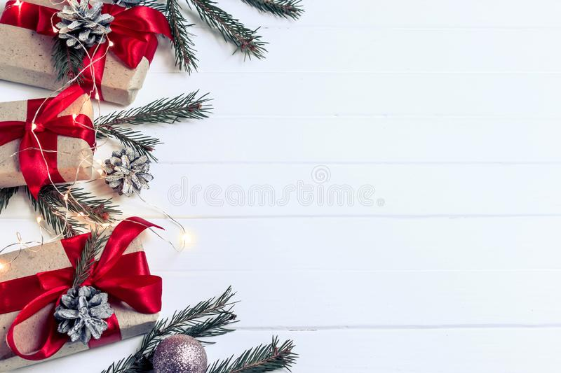 Christmas background concept. Top view of Christmas gift box with spruce branches, pine cones, red berries on white wooden table royalty free stock photography