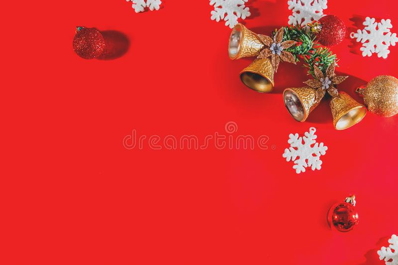Christmas background concept. Top view of Christmas golden bells with balls decoration, spruce branches, star and snowflakes on re. D background. Flat lay, top stock image