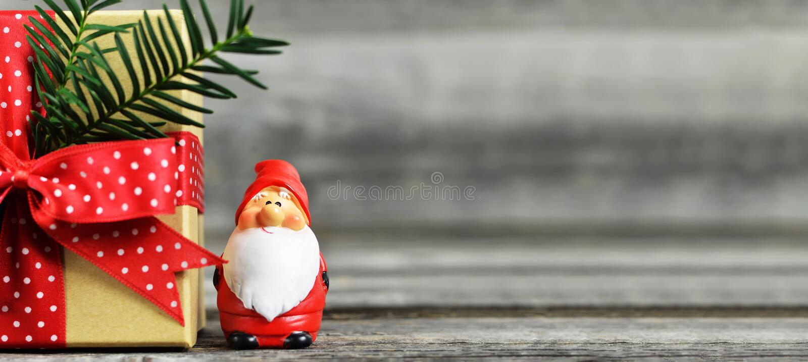 Christmas background with copy space. Santa Claus figurine and Christmas gift on wooden background. Christmas background with copy space.Cute Santa Claus royalty free stock photography