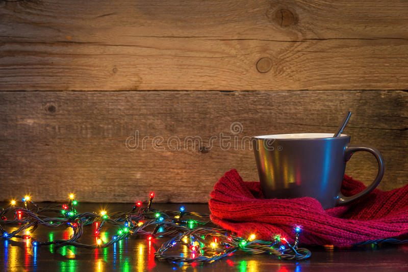 Christmas background with cup wrapped in red scarf and lights on stock photography