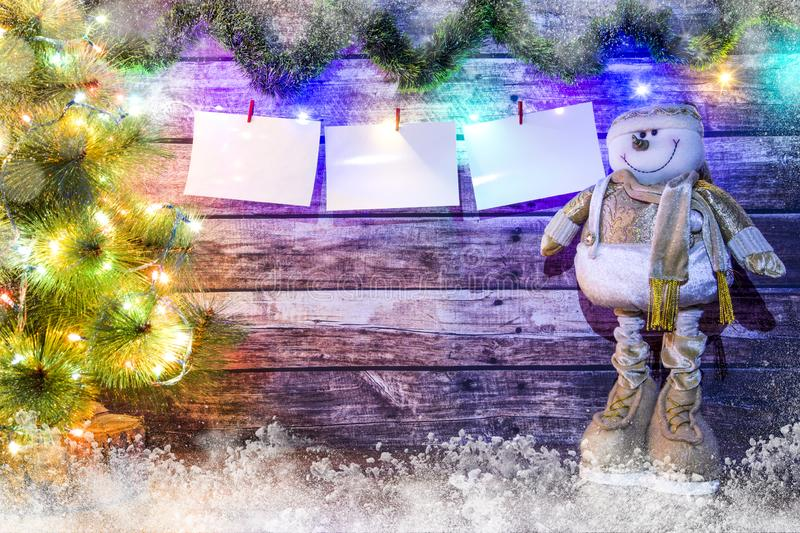 Christmas background of dark wooden boards, fir-tree, snowman and luminous garland with colored lights and Christmas balls, blank royalty free stock image
