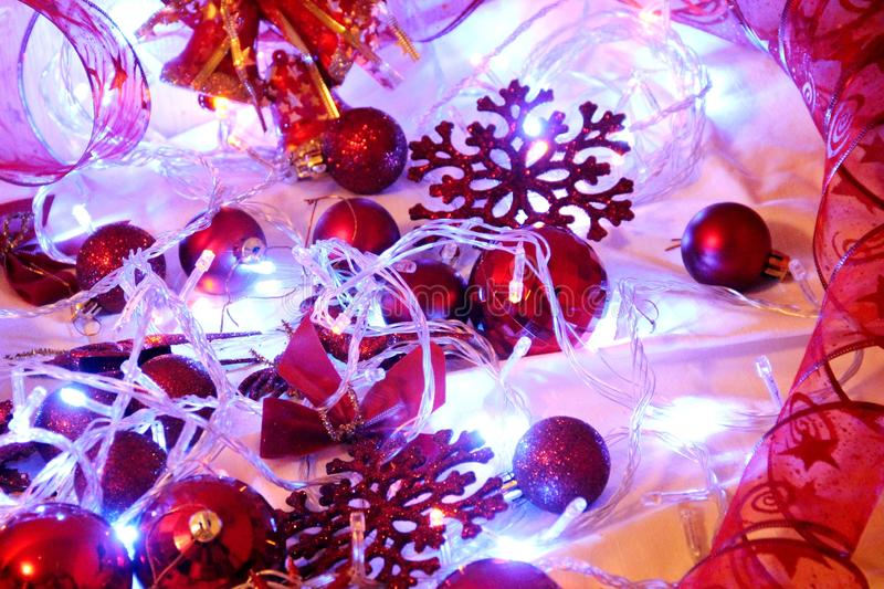 Christmas background is decorated with lights of garlands, sparkling red balls, snowflake and decorative. Background is decorated with lights of garlands stock photography