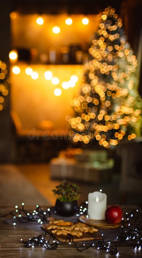 Christmas background - decorated with lights and garlands Christmas tree in the house. In the foreground is a table with ginger biscuits and a garland. Blurred royalty free stock photo