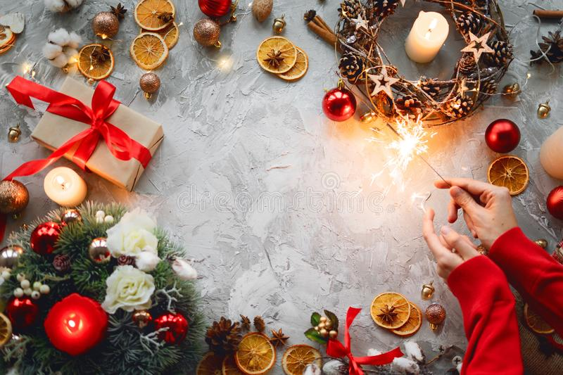 Christmas background with decorations, hands, sparkler, red gift box, orange and light candles. Top view of wreath. Flat lay. Copy stock photos