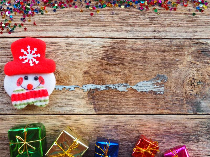 Christmas background decorations with Snowman and gift boxes on the old wood board by Flat lay, top view and copy space royalty free stock photos