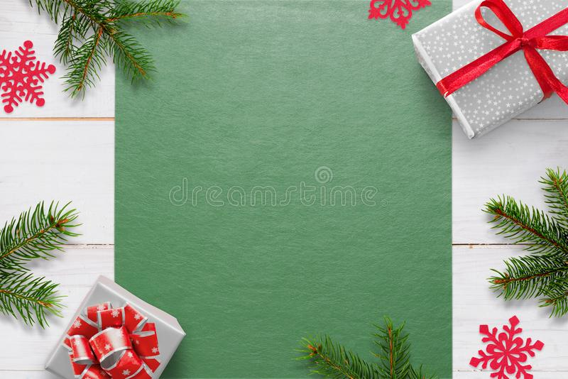 Christmas background with decorations on white wooden table and green tablecloth with free space for greeting text. Gifts, fir branches and snowflake stock photos