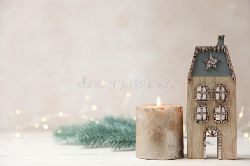 Christmas background with decorative house, candles and sprig of fir. Beautiful Christmas decor, candle and wooden house on neutral background with yellow lights royalty free stock photo