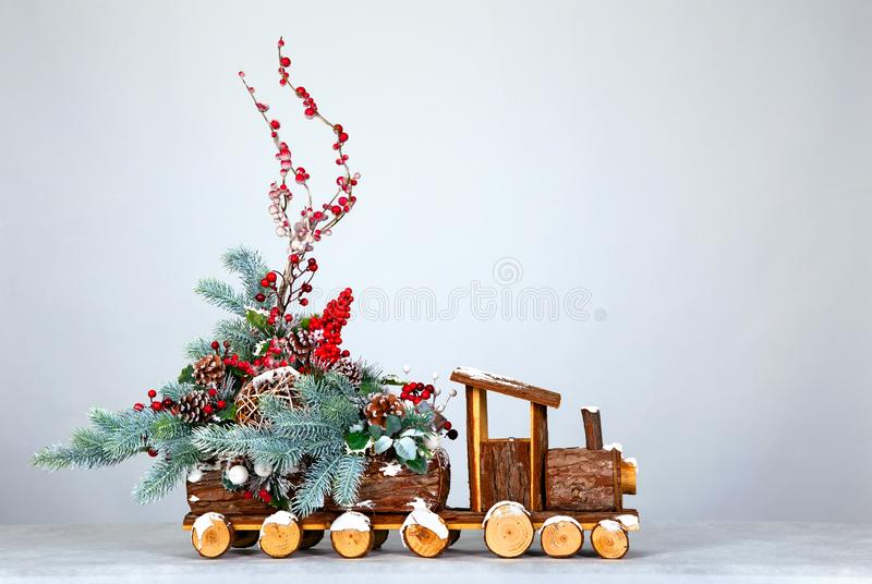 Christmas background. Decorative steam locomotive, decorated with Christmas tree branches, toys and berries royalty free stock images