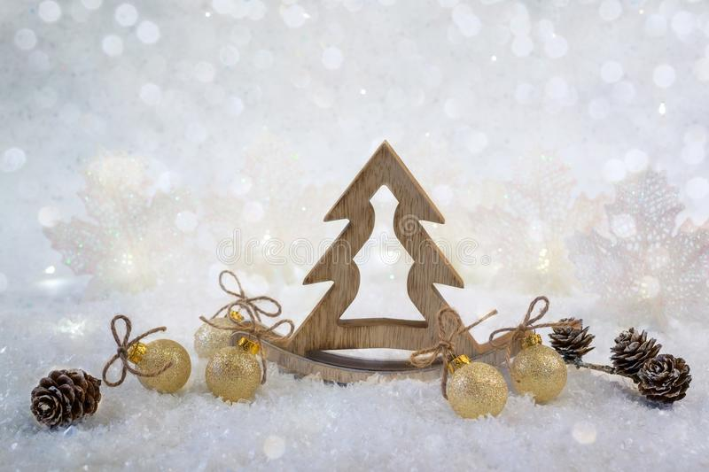 Christmas background with decorative wooden tree and golden glitter ornaments. On the snow background royalty free stock images