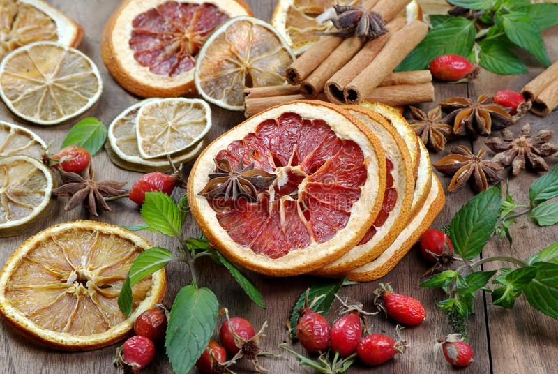 Christmas background. dried lemon, orange, grapefruit, anise stars, mint leaves, cinnamon, and rose hips on a wooden table. spices stock photo
