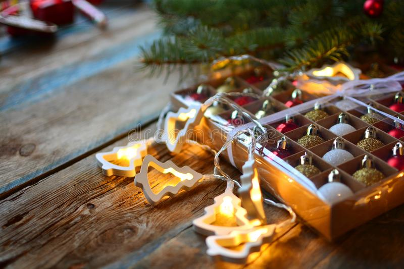 Christmas background with electric garland and xmas balls on a wooden rustic table.  stock photo