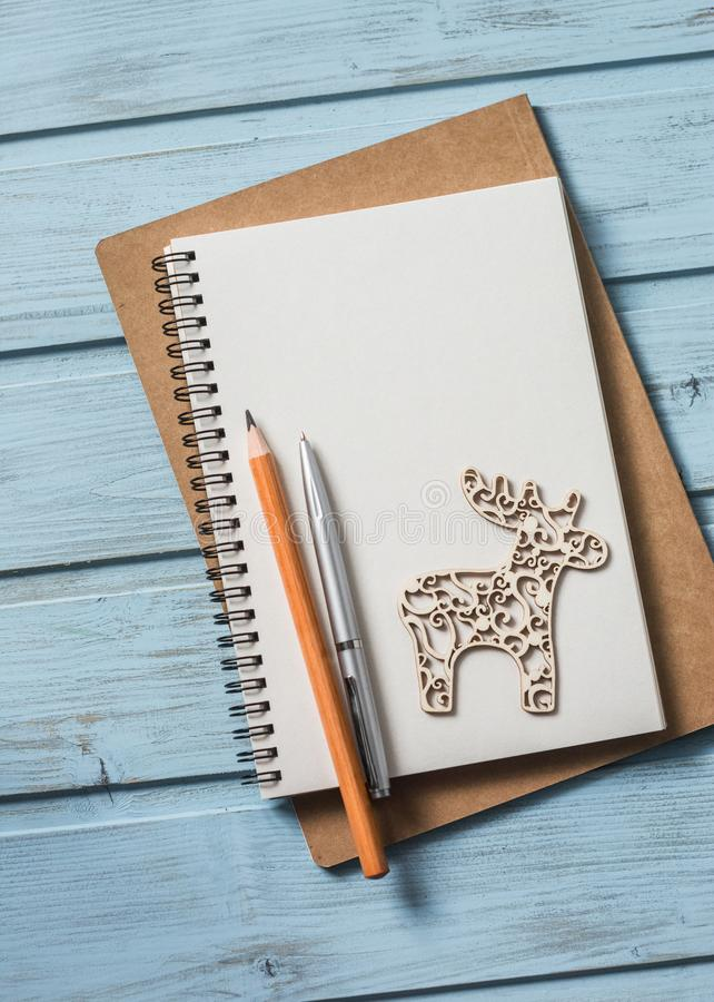 Free Christmas Background. Empty Blank Notepad, Christmas Decorations Reindeer Toy On A Blue Wooden Background. Christmas Planning Back Royalty Free Stock Photo - 103646395