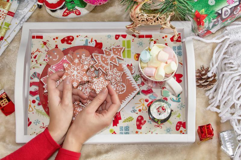 Christmas background. Female hands holding gingerbread cookies, Christmas tree, decorations and accessories. New Year stock photos