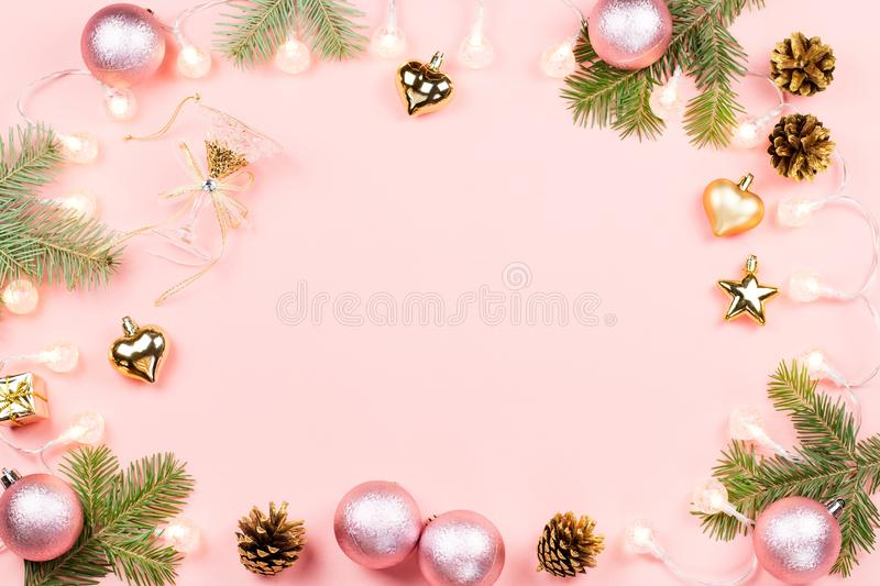 Christmas background with fir branches, lights, pink decorations on pink stock image