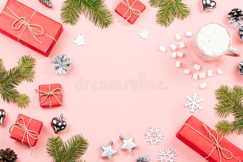Christmas background with fir branches, lights, red giftboxes, pink decorations, hot drink with marshmallows on pink stock images
