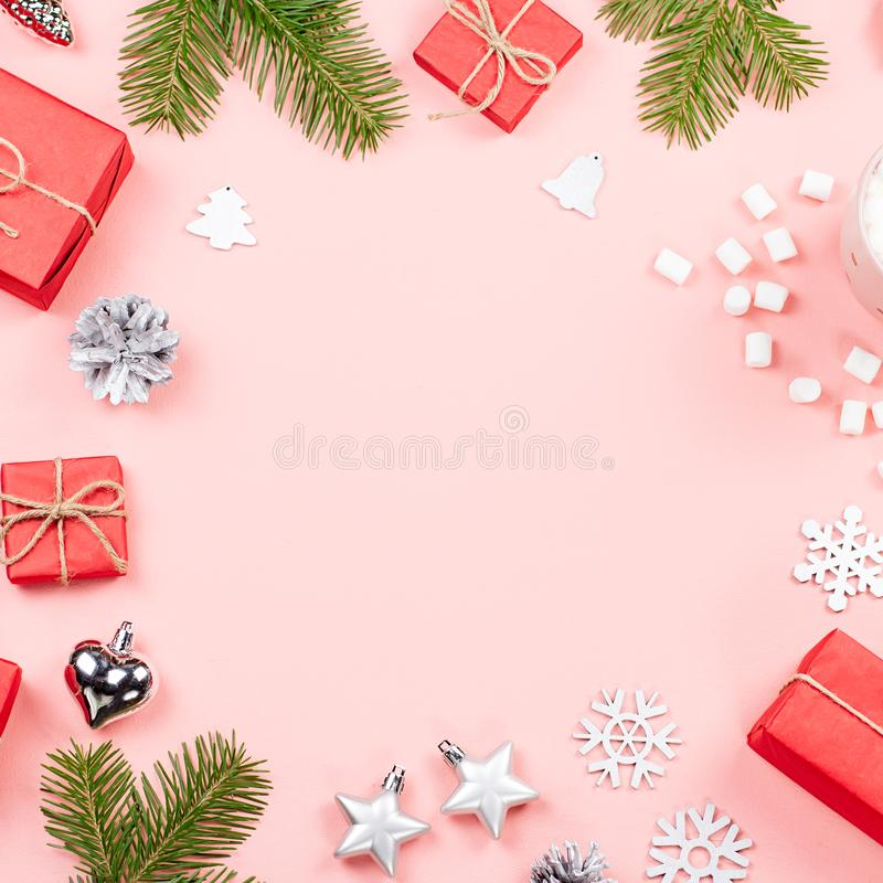 Christmas background with fir branches, lights, red giftboxes, pink decorations, hot drink with marshmallows on pink stock image