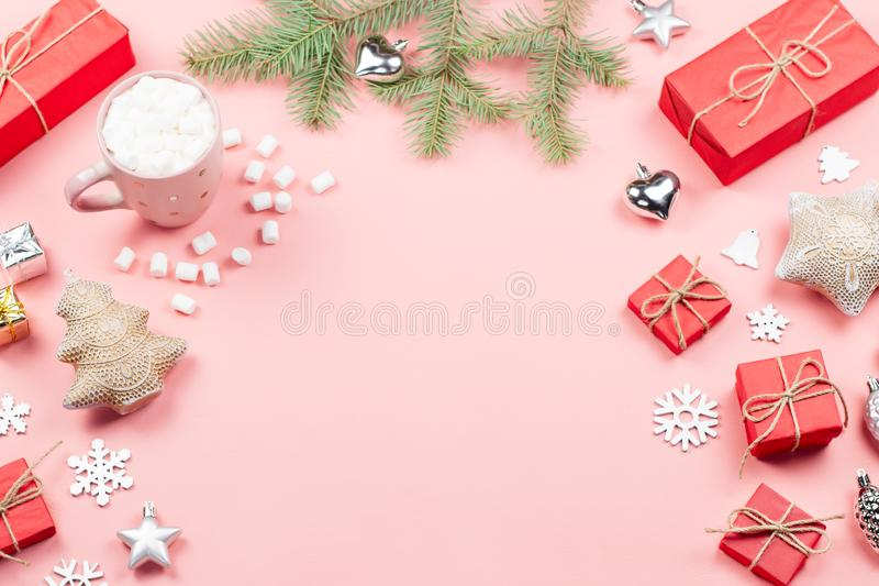 Christmas background with fir branches, lights, red giftboxes, pink decorations, hot drink with snow falling stock photography
