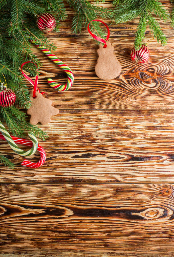 Christmas background. Fir branches, red balls, gingerbread and candy canes on the old brown boards. Rustic style. Copy space. Top view stock image