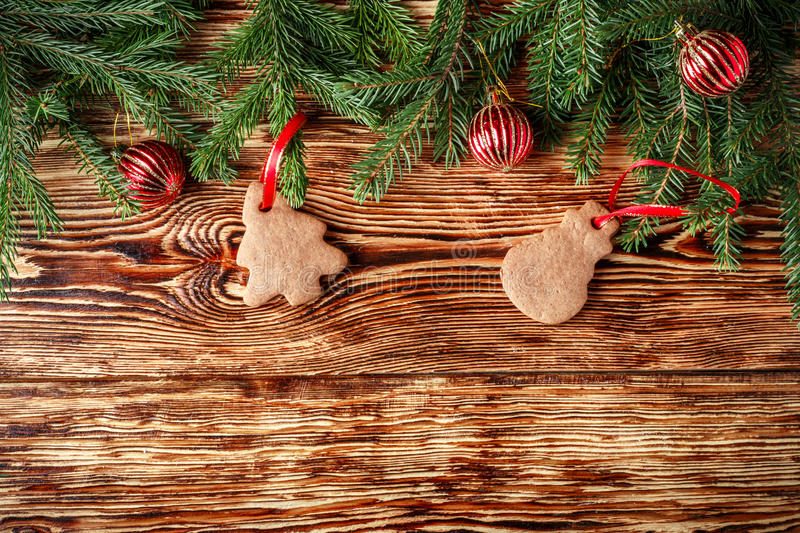 Christmas background. Fir branches, red balls, gingerbread on the old brown boards. Rustic style. Copy space. Top view stock images