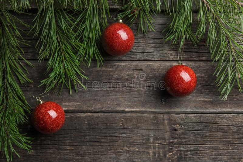 Christmas background. Fir tree branch red Christmas ball decorations at wooden table. stock photo