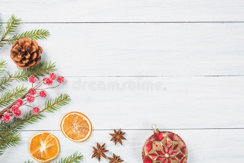 Christmas background. Fir tree branches with dried orange, anise stars, christmas ball and cone on white wooden background. Top vi stock photography