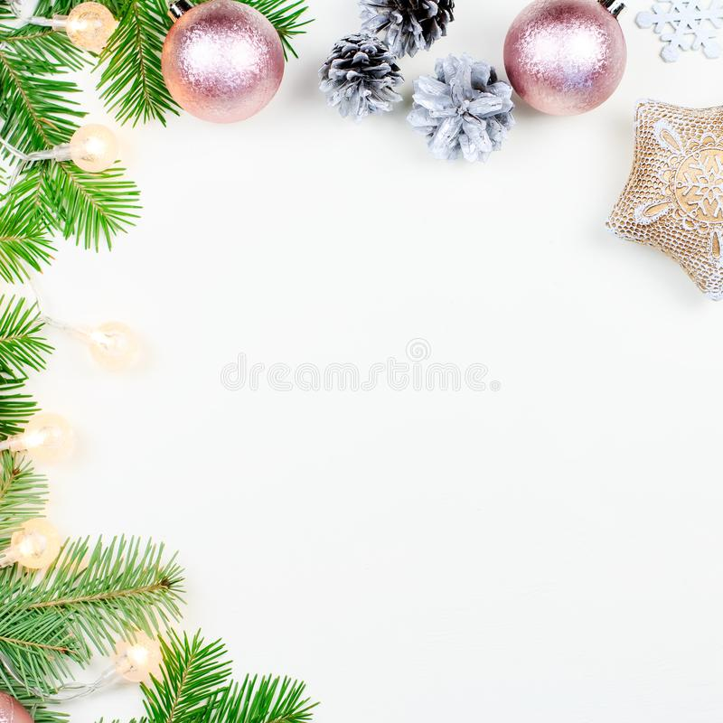 Christmas background with fir tree branches, Christmas lights, pink and beige decorations, silver ornaments stock photo