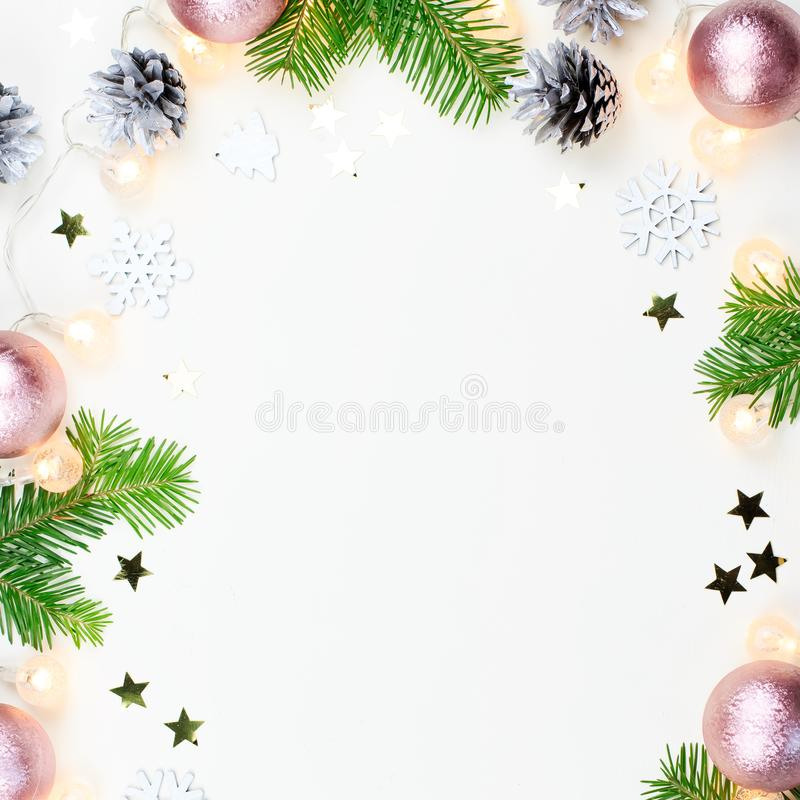 Christmas background with fir tree branches, Christmas lights, pink and beige decorations, silver ornaments royalty free stock images