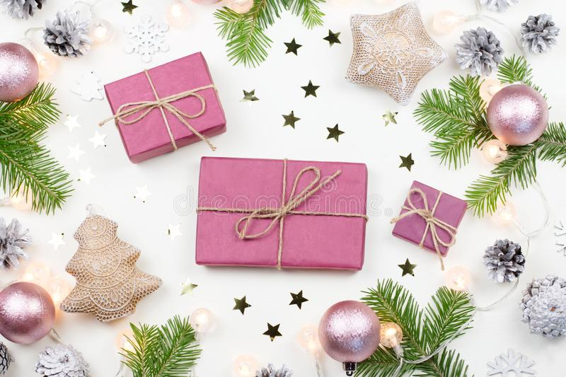 Christmas background with fir tree branches, purple giftboxes, Christmas lights, pink decorations, silver ornaments royalty free stock image