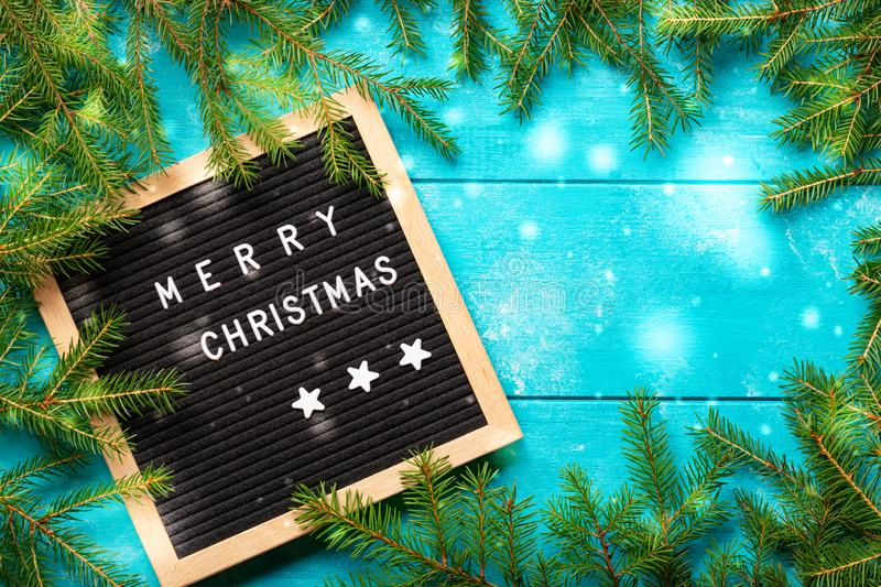 Christmas background. Christmas fir tree branches with snow on blue rustic wooden board near letter board with words Merry. Christmas stock images