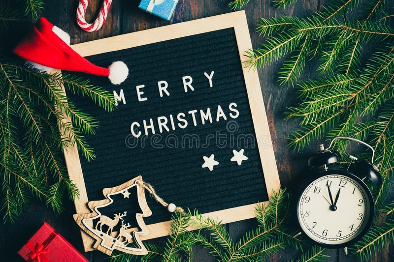 Christmas background. Christmas fir tree branches with vintage alarm clock and giftboxes on rustic wooden board near letter board royalty free stock photos