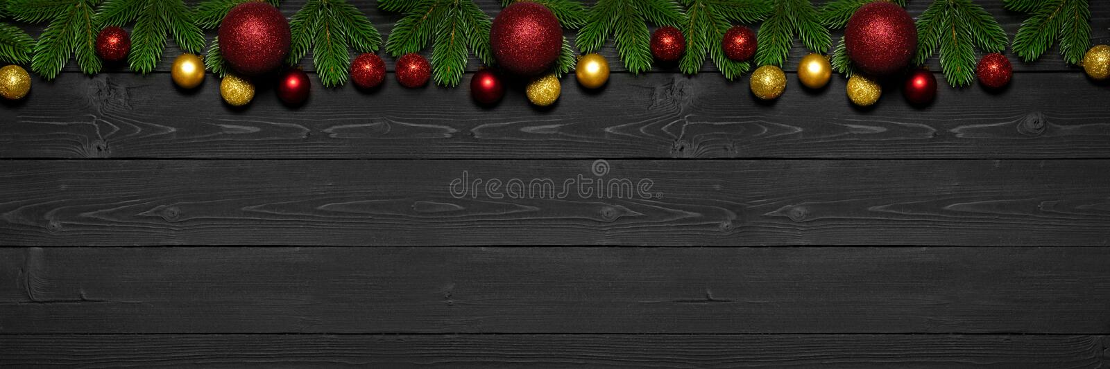 Christmas background with fir tree branches and xmas ornament bauble on dark wooden board. Holiday Christmas composition royalty free stock photos