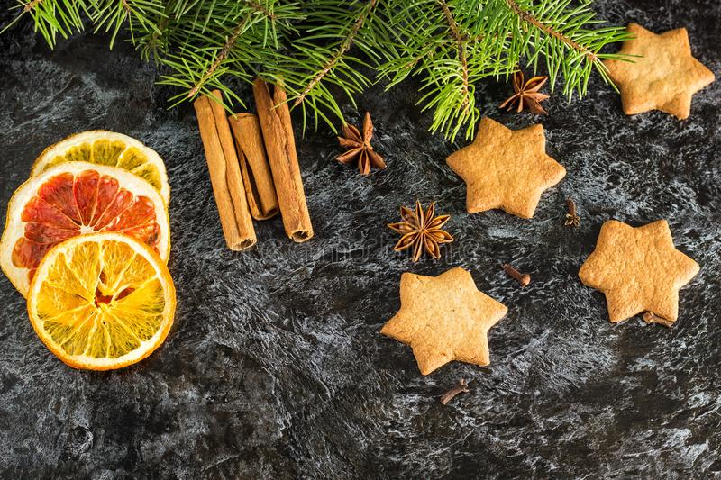 Christmas background with fir tree dry orange cinnamon anise and star of Gingerbread cookies on dark background royalty free stock photography