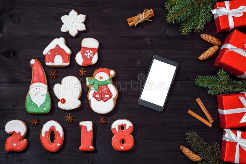 Christmas background with fir tree made from gingerbread cookies, mobile phone with blank white screen and red gifts on wooden. Background, copy space. New Year stock image