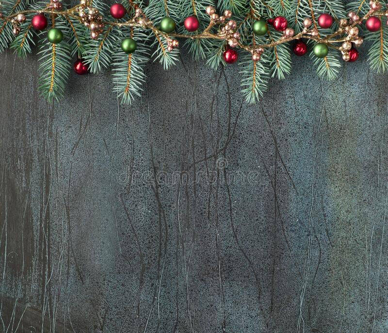 Christmas background with fir twigs, red and green baubles and bronze garland on dark, copy-space stock images