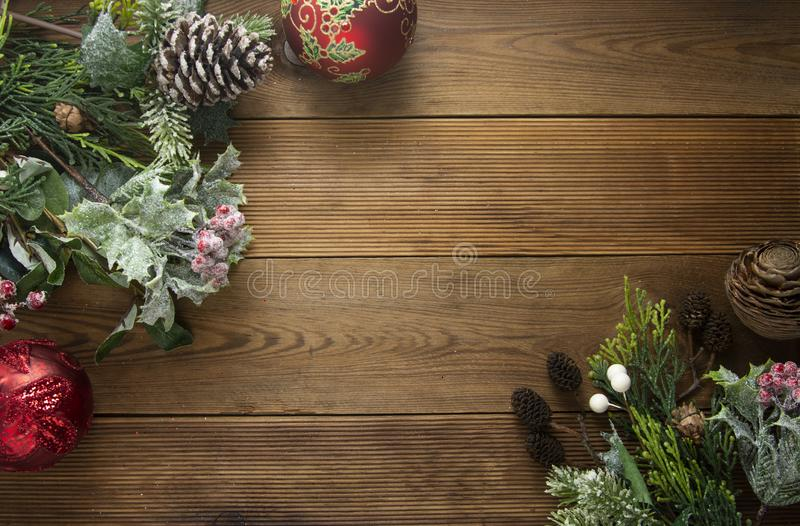 Christmas background, frme, border mock up. Pine cones, fir brances, red baubles on brown wooden table with copy space. Christmas. Christmas background, frme royalty free stock photography
